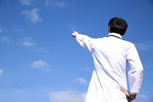 空を指さす医師